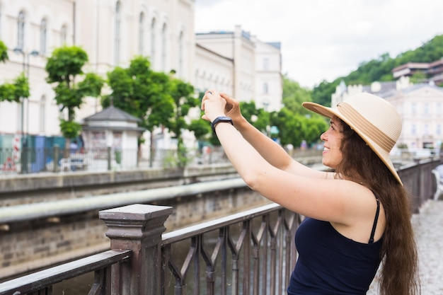 Vrouw die foto's maakt met smartphone. stijlvolle zomer reiziger vrouw in hoed met camera buiten in europese stad, oude stad karlovy vary op de achtergrond, tsjechië, europa.