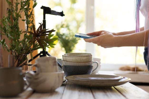 Vrouw die foto's maakt van keramisch keukengerei
