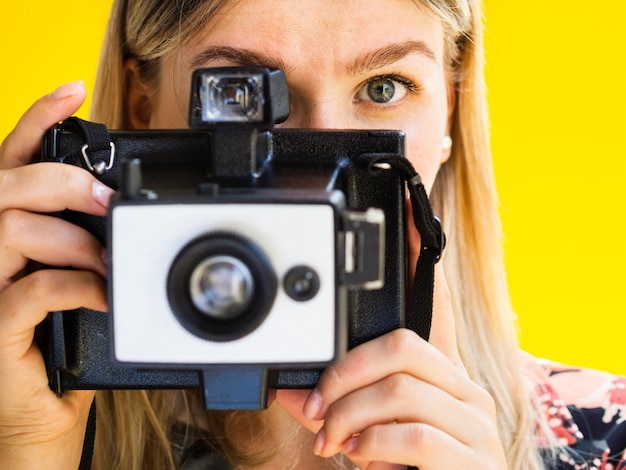 Vrouw die foto's met een retro fotocamera neemt