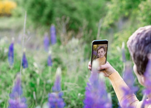 Vrouw die foto's van purpere lupines op de telefoon op het groene gras bij zonsondergang neemt