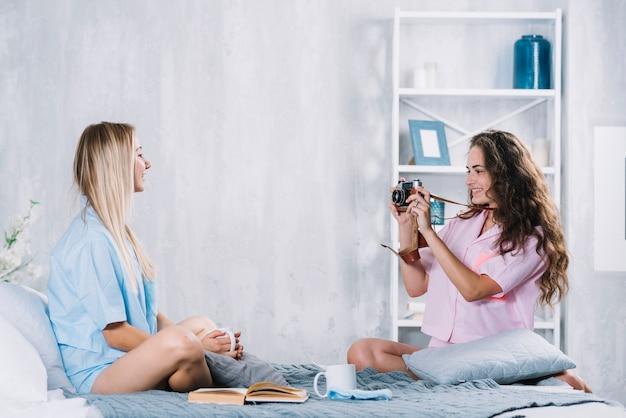 Vrouw die foto van haar vriend met camera neemt