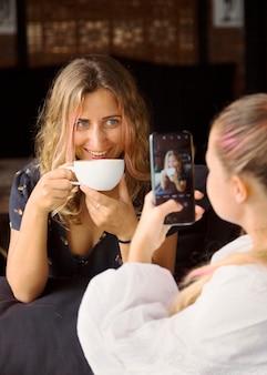 Vrouw die foto van haar vriend neemt terwijl ze een kopje koffie drinkt