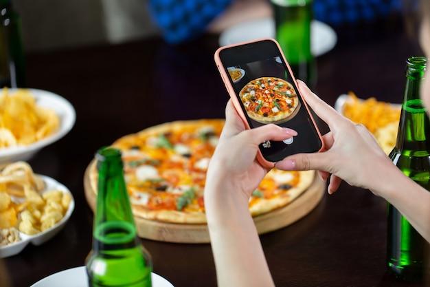 Vrouw die foto van pizza met slimme telefoon neemt