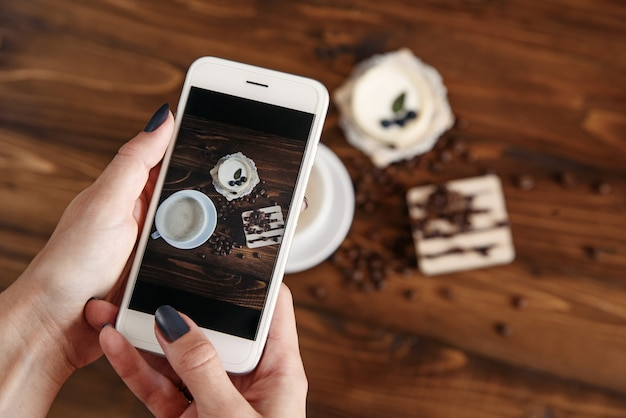 Vrouw die foto van snacks met haar smartphone neemt