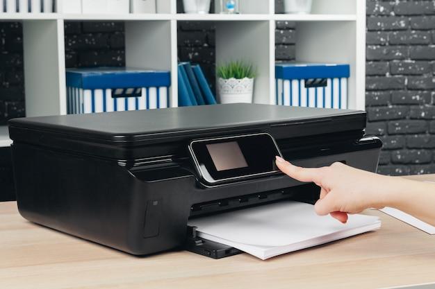 Vrouw die fotokopie maakt die kopieerapparaat in bureau met behulp van