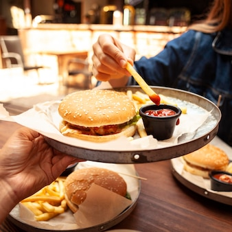 Vrouw die frietjes met ketchup eet