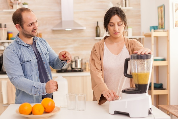 Vrouw die fruit in smoothiemaker mengt terwijl echtgenoot melkfles opent. gezonde, zorgeloze en vrolijke levensstijl, dieet eten en ontbijt bereiden op een gezellige zonnige ochtend