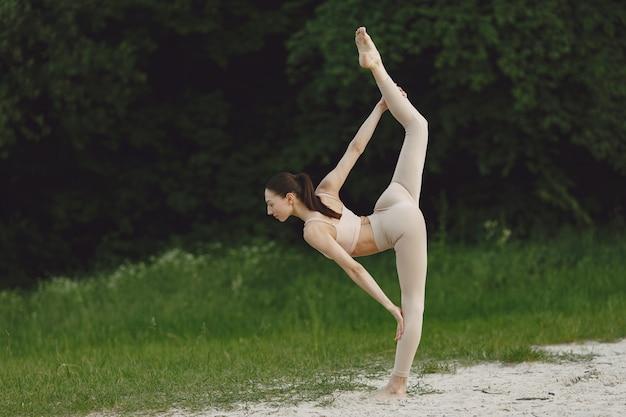 Vrouw die geavanceerde yoga in een strand uitoefenen