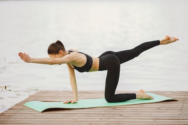 Vrouw die geavanceerde yoga uitoefenen door het water