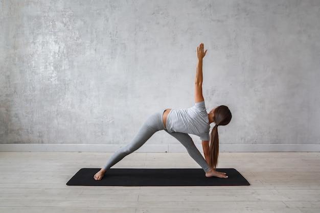 Vrouw die geavanceerde yoga uitoefenen.
