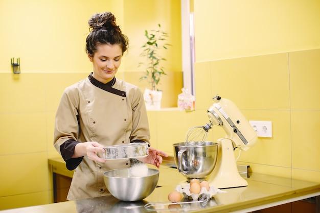 Vrouw die gebakjes voorbereidt. banketbakker in een jas. Gratis Foto