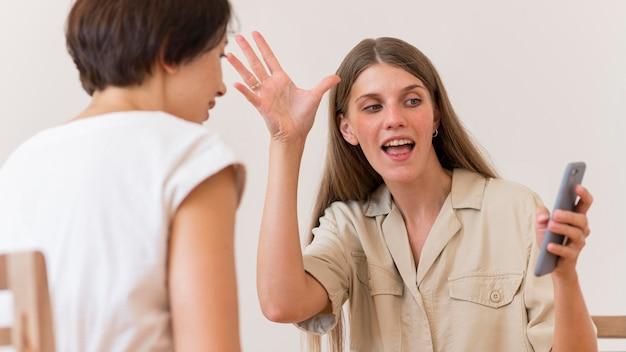 Vrouw die gebarentaal onderwijst aan een andere persoon die smartphone gebruikt
