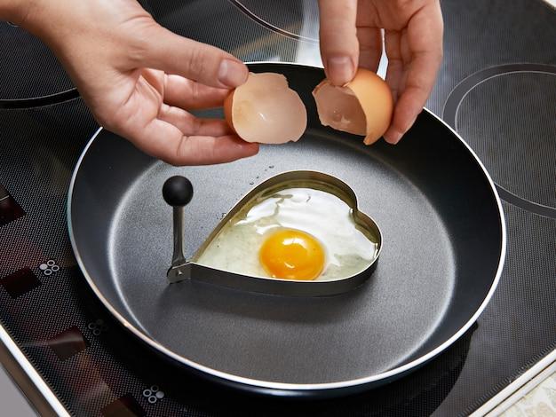 Vrouw die gebraden eieren in hartvorm voorbereidt