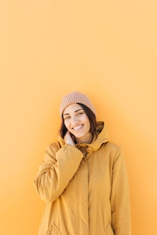 Vrouw die gebreide hoed draagt die camera bekijkt die zich tegen gele achtergrond bevindt