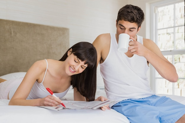 Vrouw die geclassificeerde advertenties in krant merken en man die kop thee in slaapkamer hebben