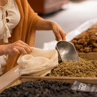 Vrouw die gedroogd voedsel bij marktplaats koopt