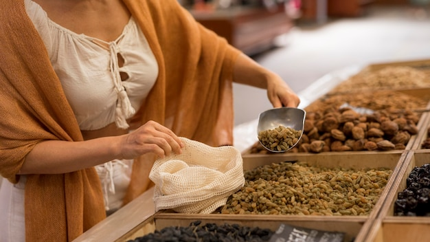 Vrouw die gedroogd voedsel op de markt zijwaarts neemt