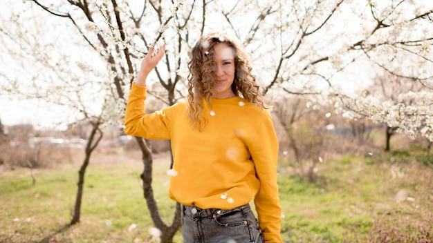 Vrouw die geel overhemd en bloemen draagt