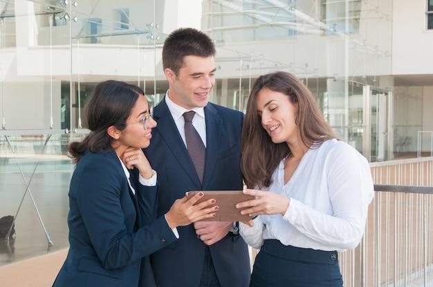 Vrouw die gegevens over tablet, collega's tonen die betrokken kijken
