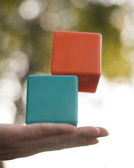 Vrouw die gekleurde plastic kubussen in evenwicht brengt