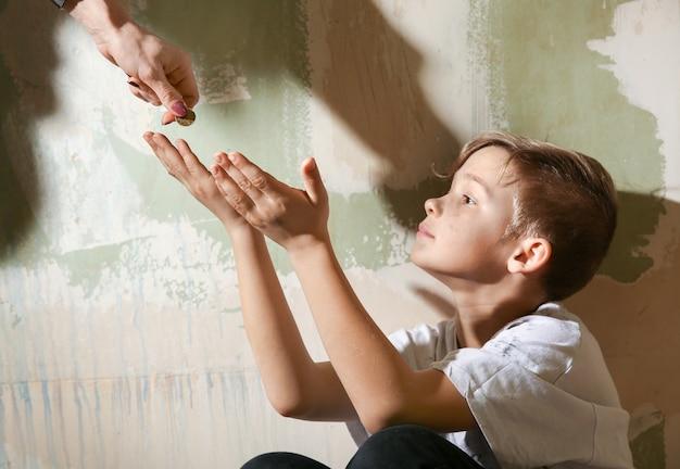 Vrouw die geld geeft aan dakloze kleine jongen binnenshuis