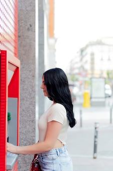 Vrouw die geld opneemt van creditcard bij atm