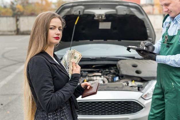 Vrouw die geld telt om voor autoservice te betalen