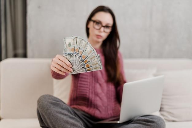 Vrouw die geld thuis op een laag met laptop verdienen