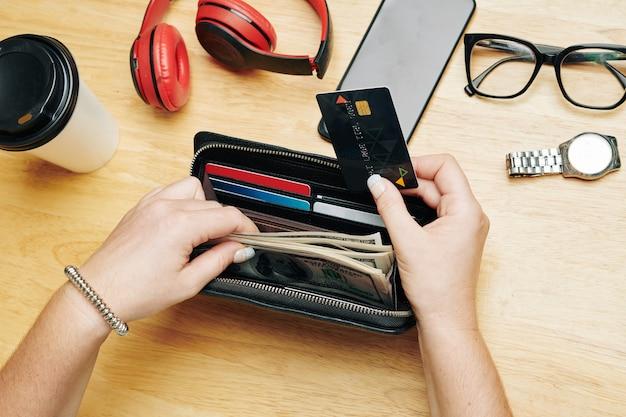 Vrouw die geld uit de portemonnee haalt