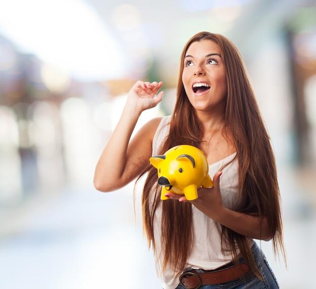 Vrouw die gele biggetje spaarpot.