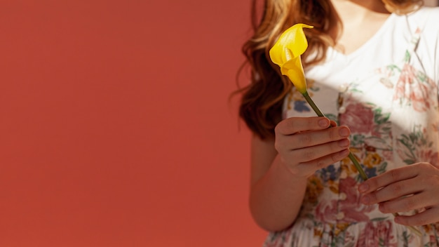 Vrouw die gele calla lelie houdt