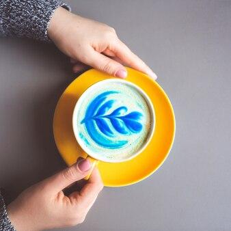 Vrouw die gele hete trendy blauwe latte met de bloemblaadjes van de kunstbloem op het schuim op grijze lijst houden