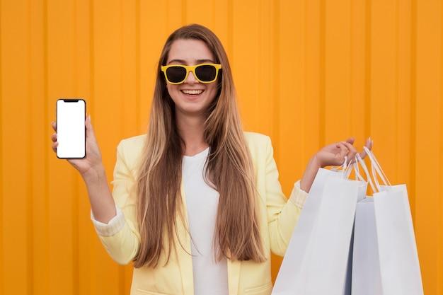 Vrouw die gele kleren draagt en een telefoon houdt