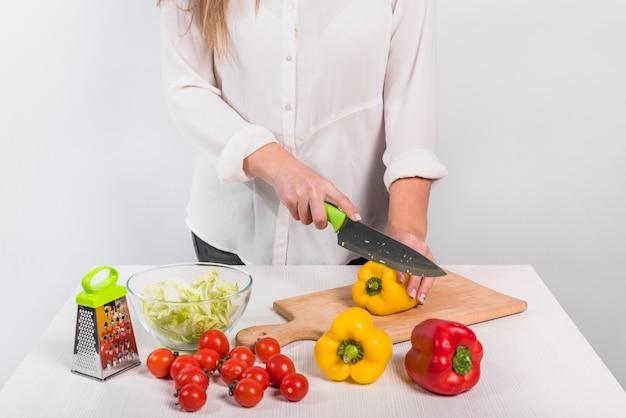 Vrouw die gele peper op houten raad snijdt