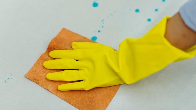 Vrouw die gele rubberen handschoenen draagt en het oppervlak schoonmaakt
