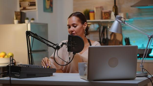 Vrouw die geluid opneemt in de thuisstudio voor podcast. creatieve online showpresentator, video, geluidsproductiestation in huis, lifestyle-avond, web, internet, media-apparatuur, laptop.