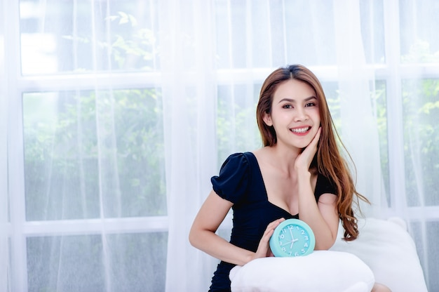 Vrouw die gelukkig in de witte slaapkamer met een wekker glimlacht