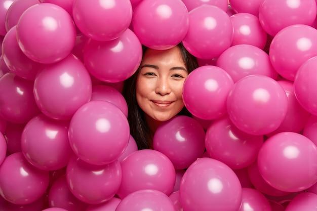 Vrouw die gelukkig is op verjaardagsfeestje omringd met roze opgeblazen ballonnen