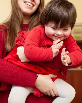 Vrouw die gelukkig kind met downsyndroom houdt