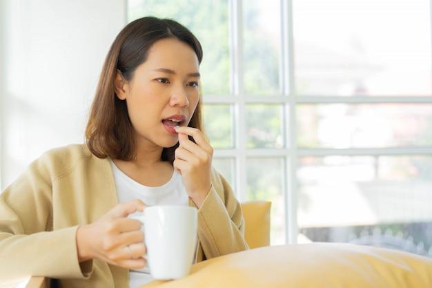Vrouw die geneeskundepil nemen om koortssymptoom in slaapkamer voor coronavirus preventief concept te genezen