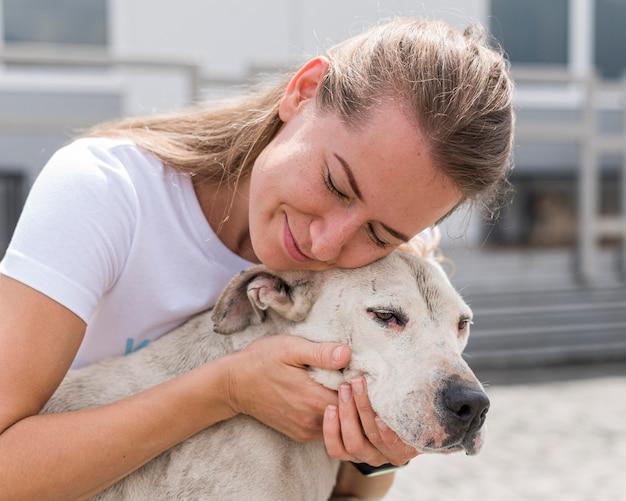Vrouw die genegenheid toont aan leuke reddingshond bij opvangcentrum