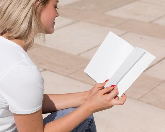 Vrouw die geniet van het lezen van een boek buitenshuis