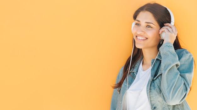 Vrouw die geniet van het luisteren muziek in hoofdtelefoon