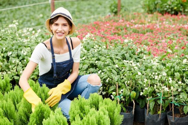 Vrouw die geniet van het werken met planten en bloemen