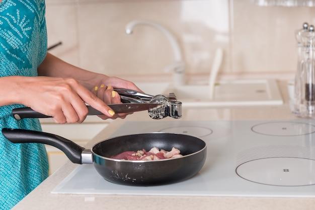 Vrouw die geplette knoflook aan voedsel toevoegt terwijl ze het vlees klaarmaakt voor het avondeten in een koekenpan op de kookplaat