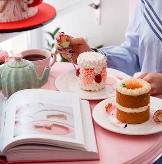 Vrouw die geportioneerde schuimgebakjecake met roze room en framboos eet