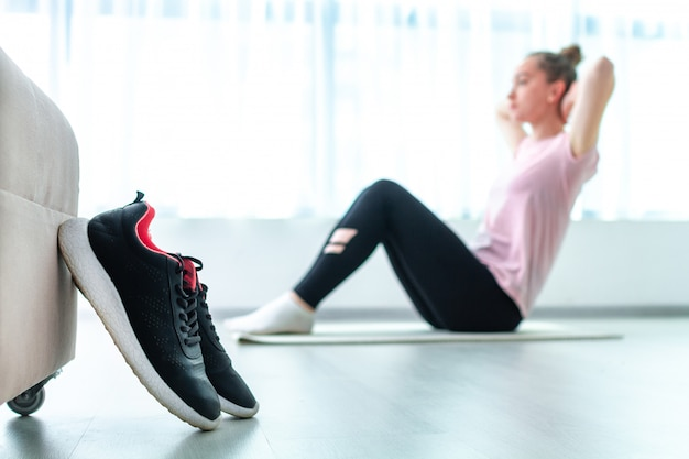 Vrouw die geschiktheidsoefeningen en training thuis op yogamat doet. afvallen en fit blijven. gezonde, sportieve levensstijl