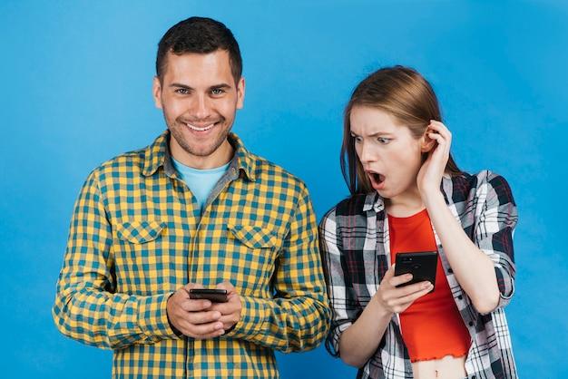Vrouw die geschokt kijkt terwijl het bekijken de telefoon van haar vriend