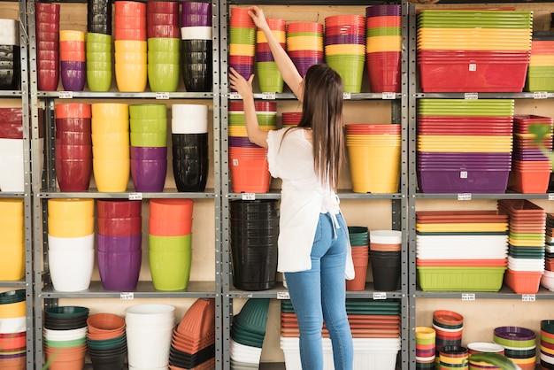 Vrouw die gestapelde bloeiende potten plaatsen in plank