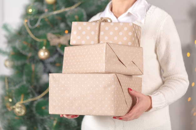Vrouw die gestapelde kerstmisgiften draagt